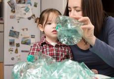 Menina que recolhe o plástico com sua mãe Imagem de Stock