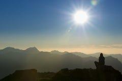 Menina que relaxa ao sentar-se na rocha no por do sol Fotografia de Stock
