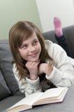 Menina que relaxa e que lê Imagens de Stock Royalty Free