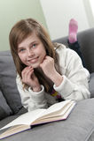 Menina que relaxa em casa e que lê Imagem de Stock