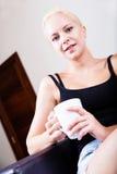 Menina que relaxa em um sofá que bebe uma xícara de café Imagens de Stock