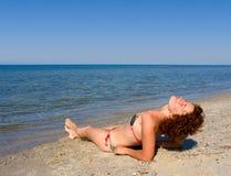 Menina que relaxa na costa de mar Imagem de Stock Royalty Free