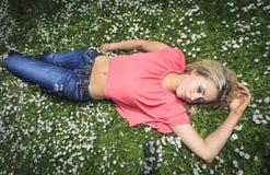 Menina que relaxa na grama Foto de Stock Royalty Free