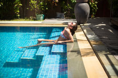 Menina que relaxa na piscina imagens de stock