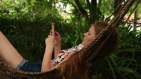 A menina que relaxa na rede usa um smartphone, balançando delicadamente perto do hotel na praia filme