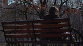 Menina que relaxa no banco no parque vídeos de arquivo