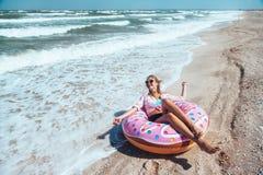 Menina que relaxa no lilo da filhós na praia fotografia de stock royalty free