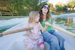 Menina que rema em um barco ao lado da mulher Imagem de Stock Royalty Free