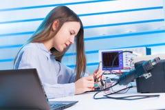 Menina que repara o dispositivo eletrónico na placa de circuito Fotos de Stock