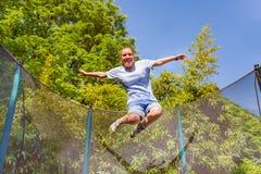 Menina que ri ao saltar no trampolim fotografia de stock royalty free