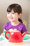 Menina que ri como joga o tea party Fotografia de Stock