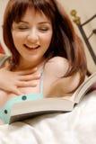 Menina que ri de seu livro Imagem de Stock
