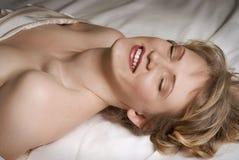 Menina que ri na cama imagem de stock