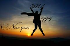 A menina que salta com ano novo feliz 2014 deseja no por do sol Fotografia de Stock