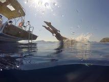 A menina que salta do mar tropical do veleiro na claro imagem de stock