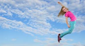 A menina que salta e que dança contra o céu nebuloso azul Imagem de Stock
