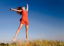 A menina que salta em um dune-1 Imagens de Stock