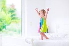 A menina que salta em uma cama Fotos de Stock Royalty Free