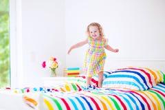 A menina que salta em uma cama Imagem de Stock Royalty Free