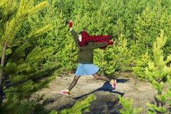 A menina que salta, floresta do pinho em um lenço vermelho na cabeça Fotografia de Stock Royalty Free