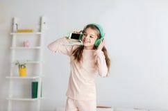 A menina que salta na cama com smartphone e fones de ouvido Fotografia de Stock