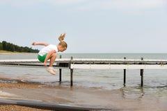 A menina que salta na costa do lago imagem de stock