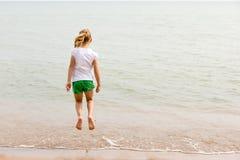 A menina que salta na costa do lago imagens de stock royalty free