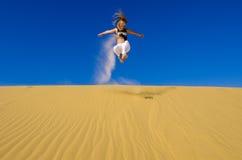 A menina que salta na duna de areia amarela Imagem de Stock Royalty Free