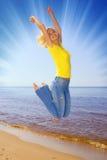 A menina que salta na praia Fotos de Stock