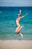 A menina que salta na praia Imagens de Stock Royalty Free