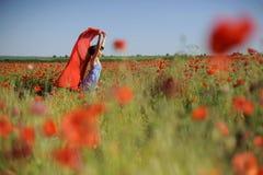 A menina que salta nas papoilas com pano vermelho Fotos de Stock Royalty Free