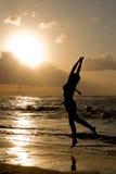A menina que salta no nascer do sol na praia fotos de stock