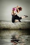 A menina que salta no telhado imagens de stock