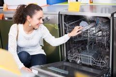 Menina que seleciona a máquina de lavar louça moderna fotografia de stock