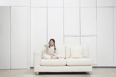 Menina que senta equipado com pernas transversal no sofá Imagens de Stock Royalty Free