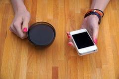 Menina que senta no café a tabela e que bebe o café preto, usando seu smartphone imagens de stock royalty free