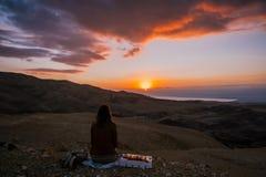 Menina que senta para baixo a opinião traseira do por do sol no deserto de Jordânia fotos de stock royalty free
