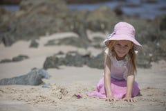 Menina que senta-se na praia Foto de Stock Royalty Free