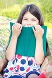 Menina que senta-se com o livro no hammock ao ar livre Imagem de Stock