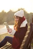 Menina que senta-se com a tabuleta no banco no parque Foto de Stock Royalty Free