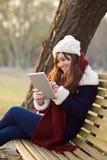 Menina que senta-se com a tabuleta no banco no parque Imagens de Stock