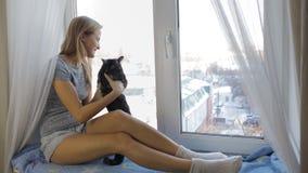 Menina que senta-se com um gato e o smotrt da janela filme
