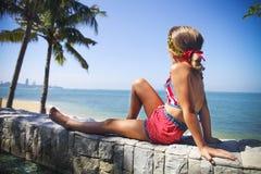 Menina que senta-se debaixo de uma palma na praia tropical Fotos de Stock