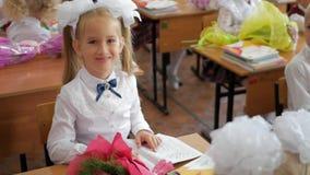 Menina que senta-se e que estuda na turma escolar Retrato da menina bonita que olha a câmera na lição video estoque
