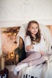 Menina que senta-se em acolhedor envolvido em uma manhã geral da árvore de Natal da cadeira em casa Imagem de Stock Royalty Free