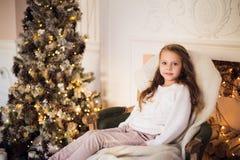 Menina que senta-se em acolhedor envolvido em uma manhã geral da árvore de Natal da cadeira em casa Imagens de Stock Royalty Free