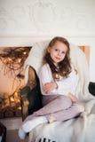 Menina que senta-se em acolhedor envolvido em uma manhã geral da árvore de Natal da cadeira em casa Fotografia de Stock Royalty Free