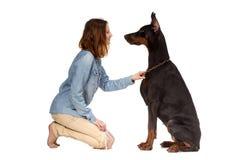 Menina que senta-se em seus joelhos na frente de um grande cão preto Imagem de Stock