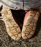 Menina que senta-se em seus pés exteriores imagem de stock