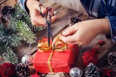Menina que senta-se em sua mesa que amarra a curva para o presente de Natal Close up das mãos e da caixa vermelha com a fita dour fotografia de stock royalty free